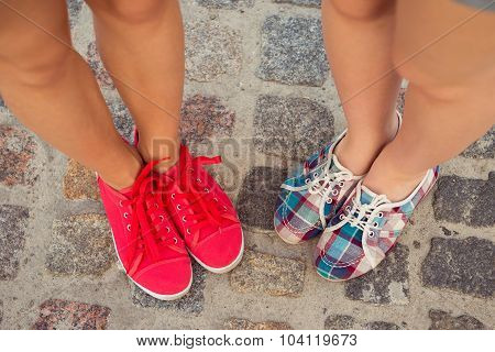 Top View Of A Two Pairs Of Sneakers Shoes Walking On Paving Ston
