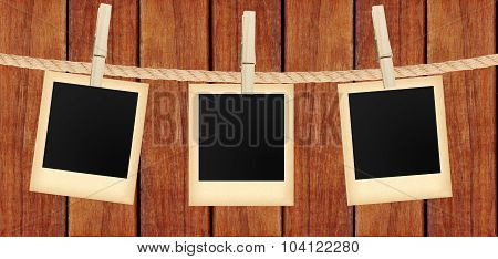 Old Photo Cards Hanging On Rope On Clothespins Over Wooden Background