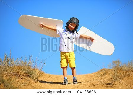 kid with wings and flying helmet plays in the plane