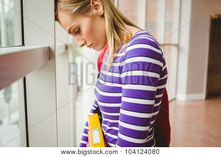 Close-up of sad female student by window in college