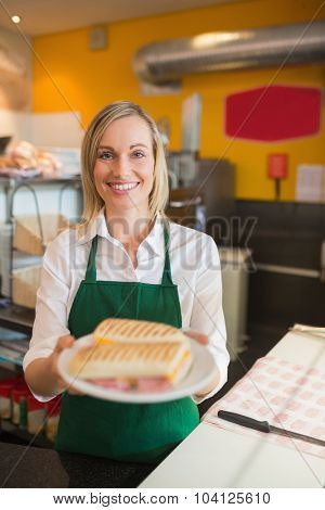 Portrait of happy female shop owner serving sandwich in plate