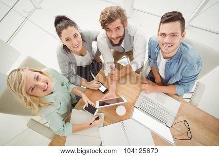 Overhead portrait of smiling business people while sitting at desk