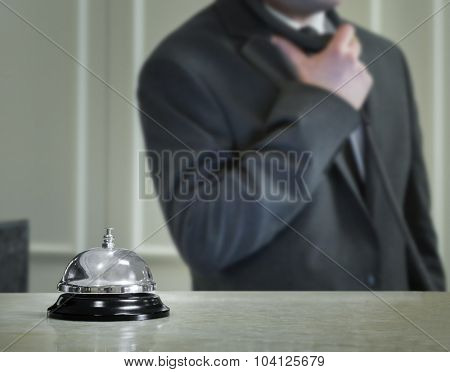 Hotel service bell and the receptionist on the phone