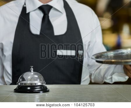 Service bell and the waiter in a restaurant with a tray in hand