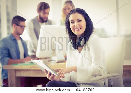 Portrait of smiling woman with headphones using digital tablet while sitting at desk in office