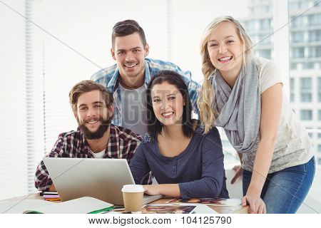 Portrait of smiling business people using laptop while sitting at desk in office