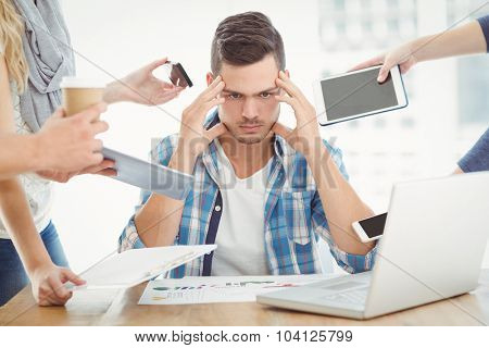 Tensed businessman with head in hand while sitting at desk