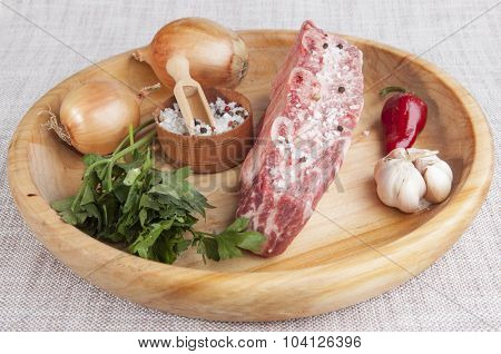 A piece of fresh marbled beef, chili pepper, parsley, onion, garlic, ribs lie on a wooden tray.