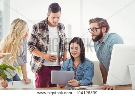 Business professionals using tablet while sitting at desk in office