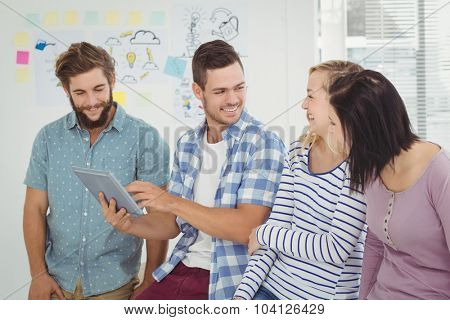 Smiling man holding digital tablet standing with coworkers at office