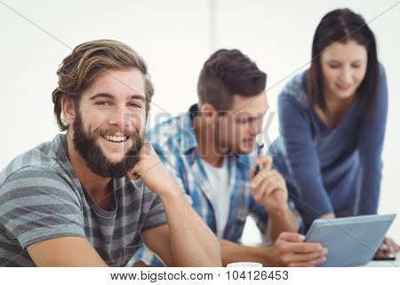 Portrait of smiling man with coworkers using digital tablet at office