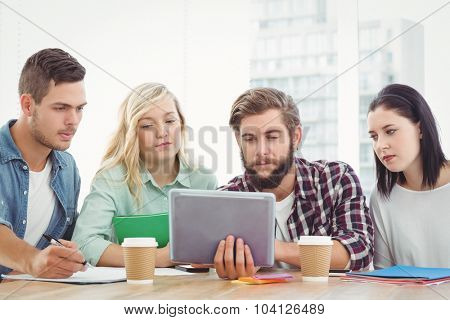 Creative business people using digital tablet while sitting at desk in office