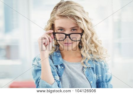Portrait of businesswoman wearing eyeglasses posing while standing in office