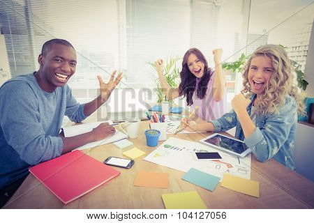 Portrait of smiling business people gesturing while sitting at desk in creative office