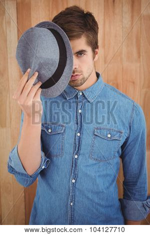 Portrait of hipster holding hat in front of face while standing against wooden wall