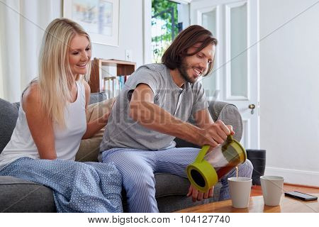 husband pouring coffee early morning breakfast routine in home living room lounge