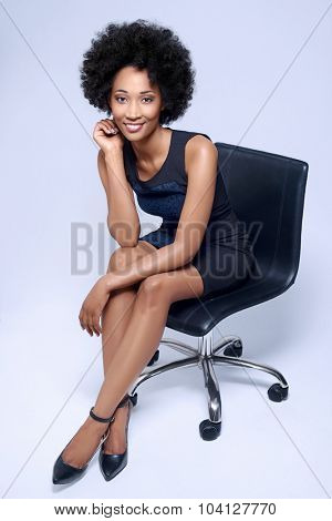 Portrait of confident black african business woman smiling and sitting on executive chair in studio, isolated on grey background