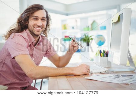 Portrait of happy hipster holding electronic cigarette at computer desk in office