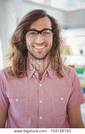 Portrait of happy man wearing eye glasses standing in office