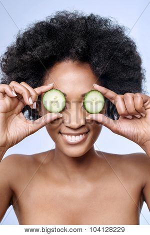 Fun cute portrait of beautiful black african model with flawless complexion smooth skin holding cucumber slices to her eyes, rejuvenating skin care regime treatment facial beauty concept
