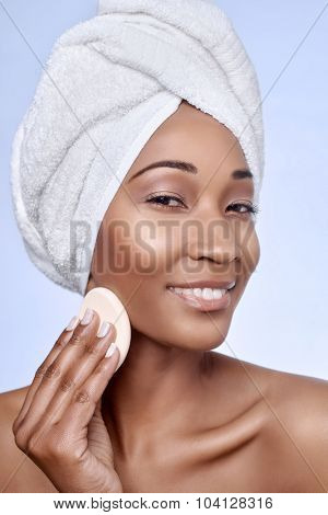 Portrait of attractive beautiful black african woman holding a make up sponge to her cheek, beauty skincare cosmetics concept