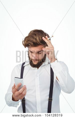 Hipster looking in mobile phone while holding cigarette against white backgrond