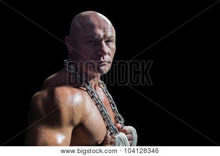 Portrait of confident bodybuilder man holding chain against black background