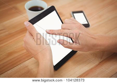 Cropped hand of man using digital tablet at desk in office