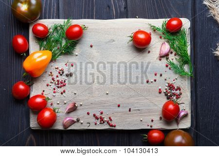 Tomatoes, pepper and herbs over wooden cutting board with empty place for text. Top view