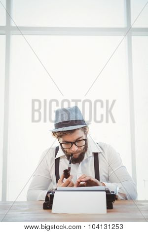 Hipster smoking pipe while working at desk against window in office