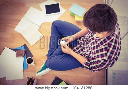 High angle view of hipster using smartphone while working in office