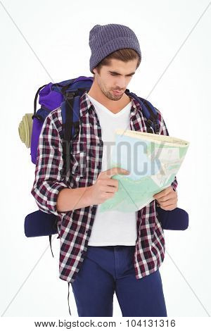 Man with backpack looking in map while standing against white background