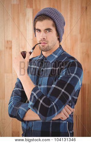 Portrait of hipster smoking pipe while standing against wooden wall in office