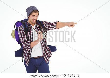 Happy man pointing while holding camera against white background