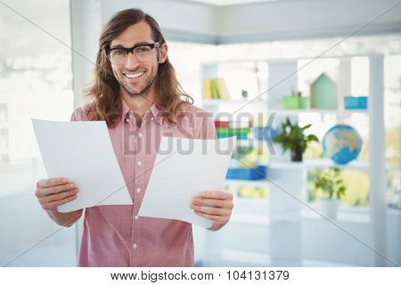 Portrait of happy hipster holding documents in office