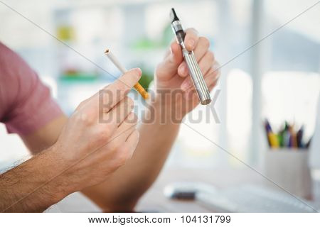Cropped image of man holding cigarettes in office