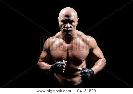 Portrait of shadow falling on muscular man against black background