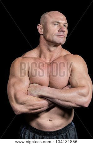 Muscular fit man with arms crossed standing against black background