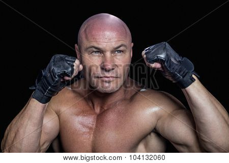 Fighter in gloves looking away against black background