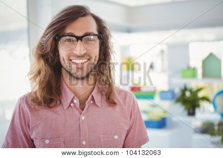 Portrait of happy hipster wearing eye glasses in creative office