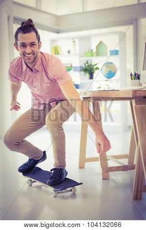 Portrait of businessman smiling while skateboarding by desk in office
