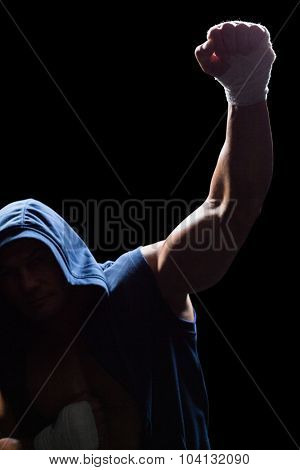 Winner athlete with arms raised against black background