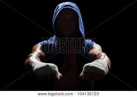 Muscular man in hood with bandage on hand against black background