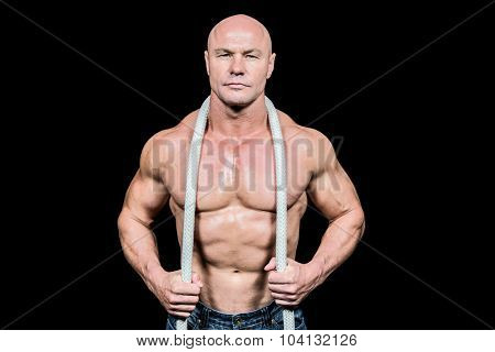 Portrait of muscular man holding rope against black background