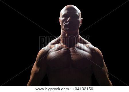 Portrait of bodybuilder standing against black background