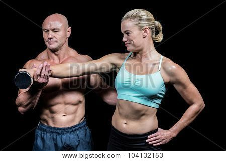 Trainer helping woman for lifting dumbbell against black background