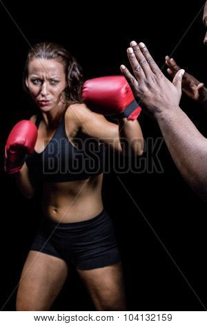 Female fighter hitting on trainer hand against black background