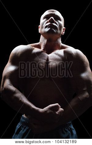Bodybuilder looking up while flexing muscles against black background
