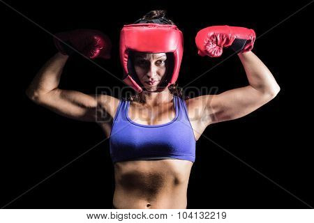 Portrait of confident female fighter flexing muscles against black background