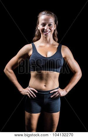 Portrait of cheerful athlete with hands on hip against black background